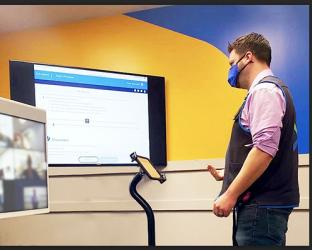 a man standing in front of a computer screen
