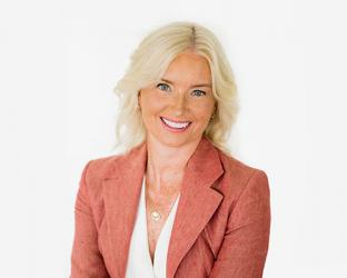 Carolyn Everson wearing a suit and tie smiling at the camera
